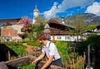 Gärtner am Polznkasparhaus mit Kirche St. Martin am Mohrenplatz in Garmisch-Partenkirchen