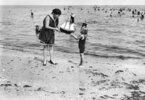 Insel Usedom, Heringsdorf: Frau überreicht kleinem Mädchen ein Modellsegelschiff am Strand