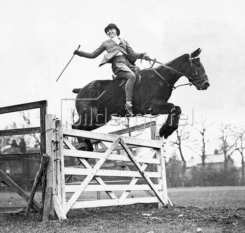Die passionierte junge Springreiterin Olive Ricks auf ihrem Pony-Pferd Peter Pan im Sprung in Addlestone, Surrey. Photographie um 1930.