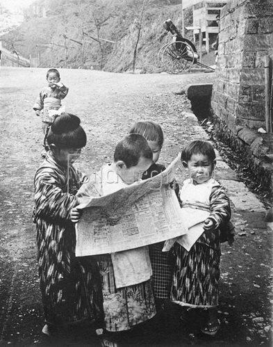 Ein Grüppchen kleiner Japaner, in bunter Tracht, sind vertieft in die Lektüre einer Zeitung. Photographie, um 1930.