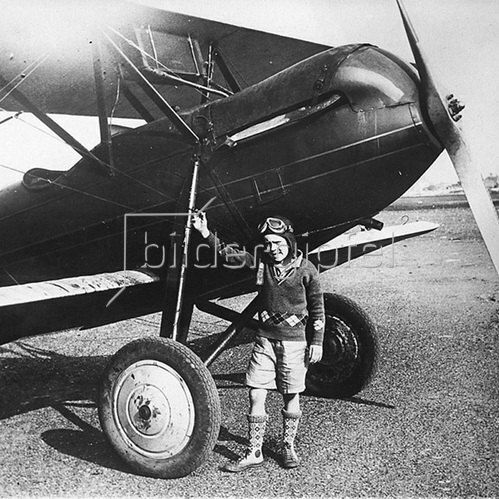 Der achtjährige Robert L. Cospey präsentiert sich vor seinem Flugzeug. Photographie. 1930