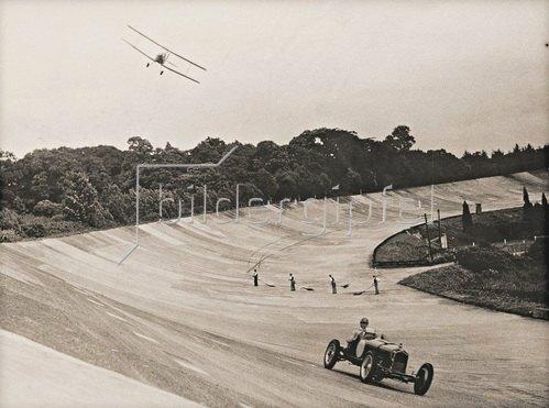 Strassenkehrer beobachten ein Duell zwischen Flugzeug und Automobil. Brooklands, 1937