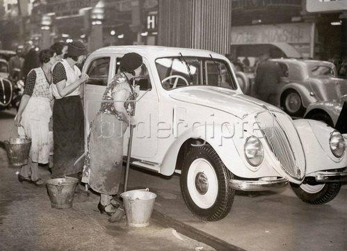Putzfrauen begutachten eine Luxus-Limousine bei der Automobilausstellung in London 1936. Photographie.15.10.1936.