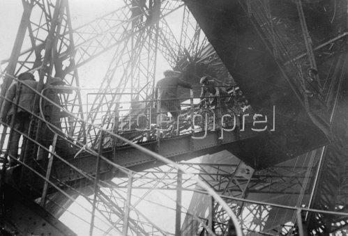 Menschen besteigen den Eiffelturm, während ein Mann mit seinem Fahrrad die Treppe hinunterfährt. Paris. Photographie. um 1930