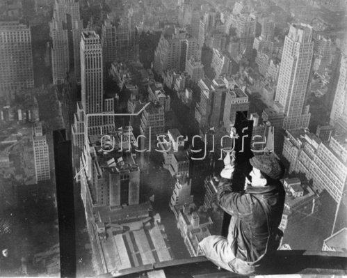 Bauarbeiter, der auf einem Gerüst sitzt, blickt über New York. Photographie. Um 1930.