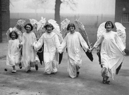 Englische Schülerinnen in Engelsflügeln auf dem Weg zu Filmaufnahmen. England. Photographie. Um 1930.