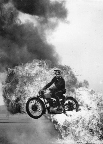 Motorradsprung durch eine Feuerwand. Photographie. Um 1935
