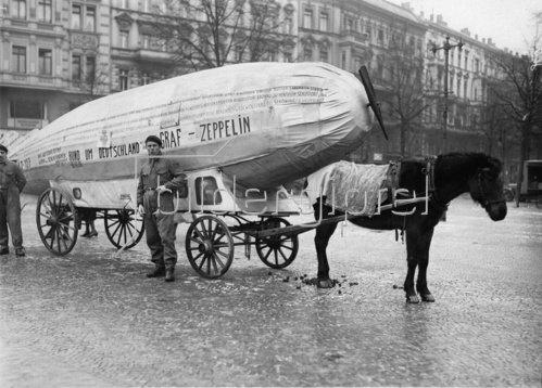 Ein miniatur-Zeppelin gezogen von einem Lasttier wirbt für Graf Zeppelins Deutschlandumkreisung. Photographie. Um 1930