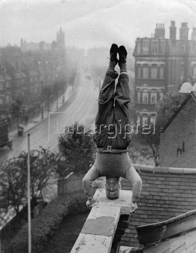 Arthur Hesth, ein Bewohner von Cricklewood, macht auf dem Dach seines Hauses einen Kopfstand. Photographie. Um 1930.