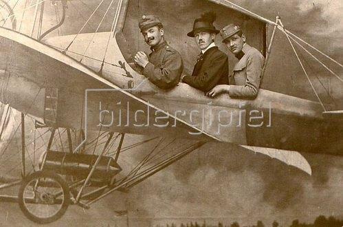 Drei Männer werden porträtiert, als Kulisse dient ein Bild von einem Flugzeug. Photographie. Um 1890.