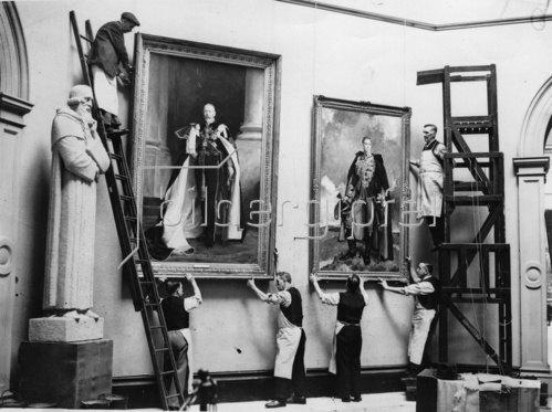 Portraitgemälde von George V. und George VI.werden in der Burlington Galerie aufgehängt. London. England. Photographie. Um 1935.