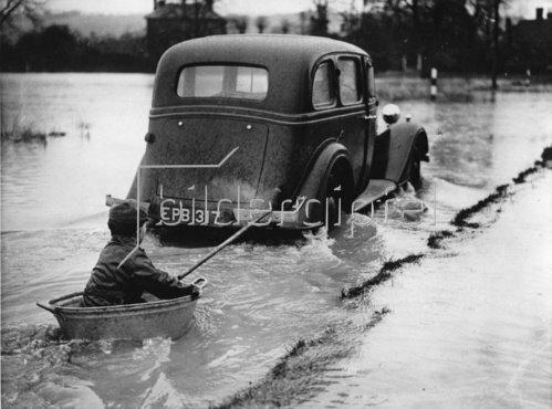 Ein kleiner Junge nützt die Überschwemmung in Yalding bei London für eine Kahnfahrt. Photographie. 1937.