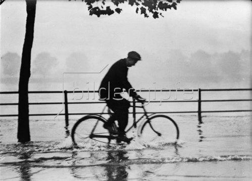 Überschwemmung an der Themse. Ein Radfahrer auf dem Weg zur Arbeit. Photographie. England. 1932.