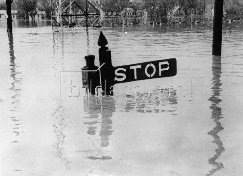 Der Ohio-Strom ist über die Ufer getreten. Nur ein Verkehrszeichen ragt aus dem Wasser. Photographie. Um 1930.