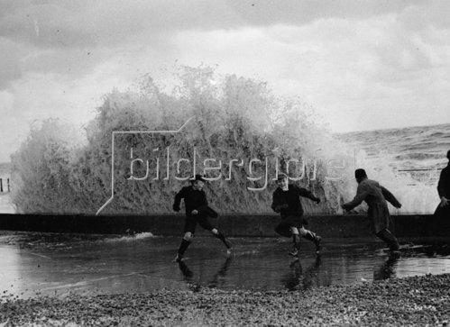 Nach dem Hochwasser in Hastings fliehen einige Buben vor den Wellen. Photographie. England. Um 1930.