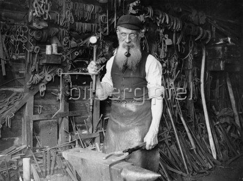 Der 74 jährige Robert Goldstone, auch Old Bob genannt, in seiner Schmiedewerkstatt in Great Stamford. Photographie. 28.8.1929.