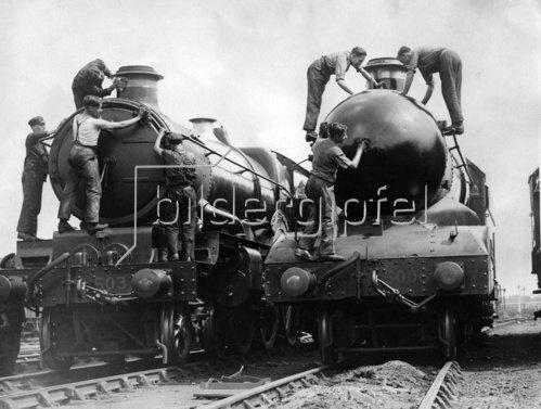 Arbeiter bei der Reinigung zweier Lokomotiven. Photographie. Um 1935.