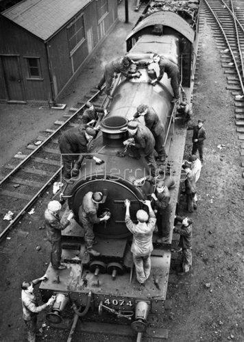 Reinigung einer Lokomotive vor den Osterfeiertagen. Photographie. Um 1935.