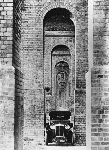 Die Zwischenräume eines neuen U-Bahnviadukts in London sind so schmal, dass ein Auto nur mit knapper Not hindurchkommt. Photographie. 16. August 1932.