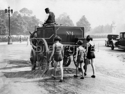 Londoner Kinder in Badeanzügen spazieren hinter einem Reinigungsfahrzeug und genießen die Abkühlung. Photographie. 1932.