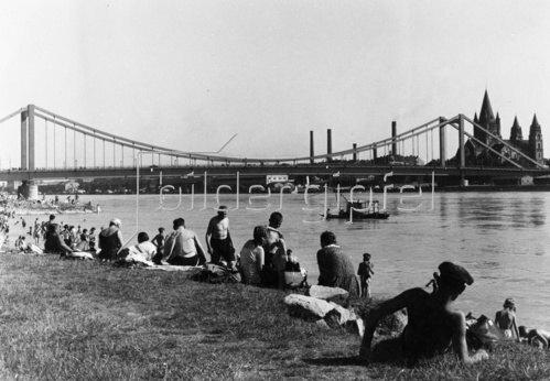 Badende an der Wiener Donau, im Hintergrund die Reichsbrücke. Wien. Österreich. Photographie. Um 1930.