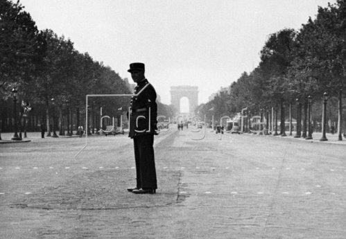 Ein Polizist steht einsam auf den Champs Elysee, da die meisten Pariser im August die Stadt verlassen. Paris. Frankreich. Photographie. Um 1930.