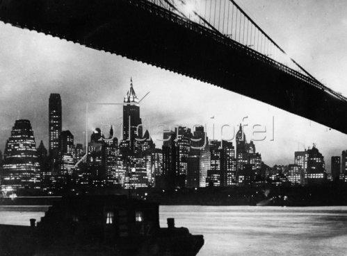Die nächtliche Skyline von Manhattan mit der Brooklyn Bridge. New York. Photographien. Um 1935.