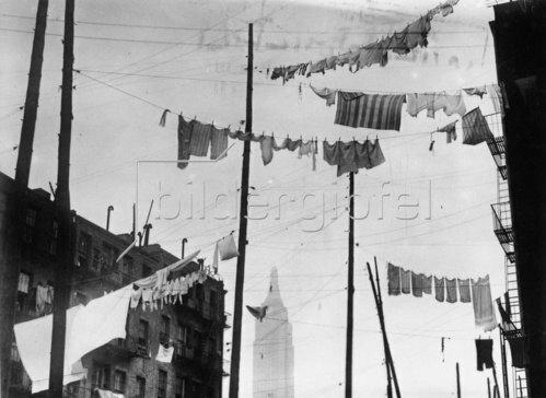 Diese Wäscheleinen befinden sich nur unweit des Empire State Buildings, das im Hintergrund auch zu sehen ist. New York. Photographie. Um 1935.
