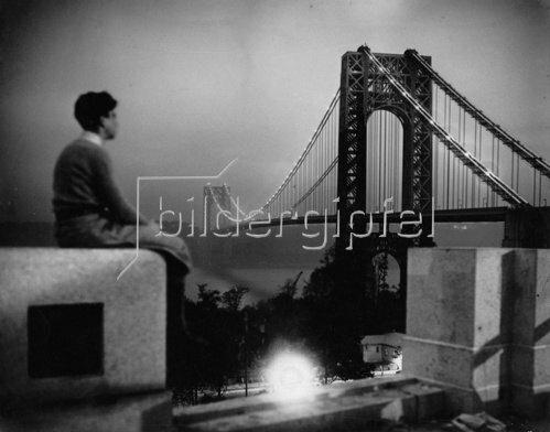 Die Wash Bridge bei Nacht. Im Vordergrund die Silhouette eines jungen Mannes. Photographie. Um 1935.