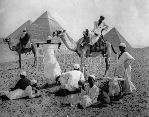 Kamele und ihre Reiter während einer Rast vor Pyramiden in Ägypten. Photographie. Um 1935.