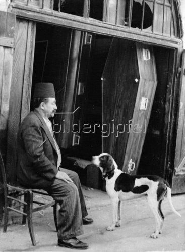 Sargverkäufer mit seinem Hund vor einer Reihe von Särgen in Jerusalem. Photographie. Um 1935.
