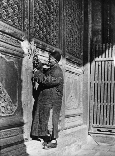 Der Hüter des Konfuziustempels in Nordchina öffnet das chinesische Schloss, um die großen Torflügel zu öffnen. Photographie. Um 1935.