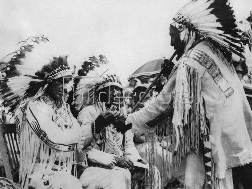 Indianer beim Rauchen einer Friedenspfeife. Photographie. Um 1930.