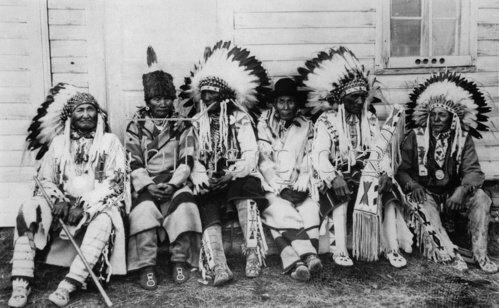 Indianer in traditoneller Stammeskleidung bei einer Konferenz im Glacier Nationalpark.  Photographie. Um 1935.
