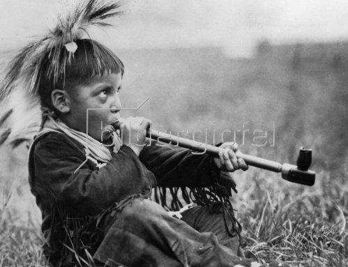 Ein kleiner Indianer raucht eine Friedenspfeiffe. Photographie. Um 1935.