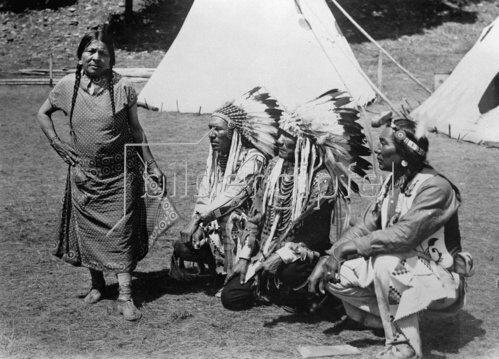 Indianer, eine Frau und drei Männer, vor ihren Zelten. Photographie. Um 1930.