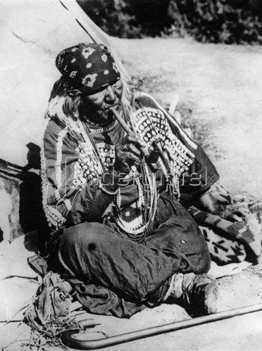 Eine alte Indianerin raucht Pfeife. Photographie. Um 1935.