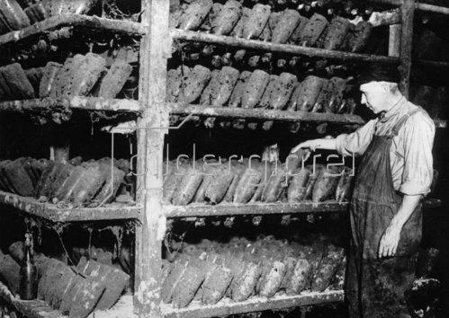 In einer Sektkellerei warten Sektflaschen auf das Ende der Prohibition. Sie müssen dort mehrmals im Jahr gedreht werden. Photographie. Um 1930.