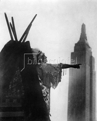 Indianer zeigt von seinem Zelt aus auf einen Wolkenkratzer. Photographie. Um 1930.