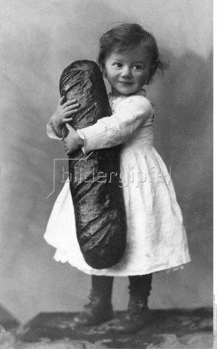 Ein kleines Kind hält einen grossen Laib Brot im Arm - 1914