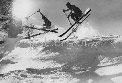 Schweiz Graubuenden Oberengadin: Wintersport, Skilaufen, Maenner springen ueber eine Gletscherspalte. 1928