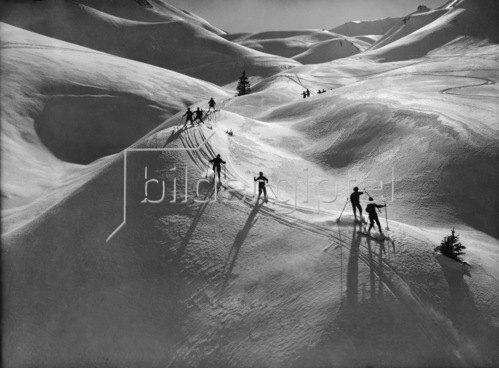 Eine Kindergruppe bei der Abfahrt im verschneiten Skigebiet, 1928