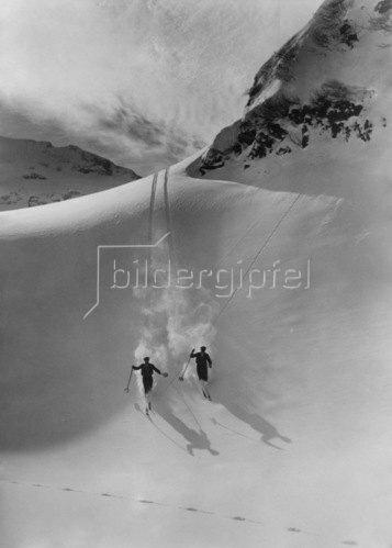 Zwei Skifahrer bei der Abfahrt im verschneiten Hochgebirge. 1933.