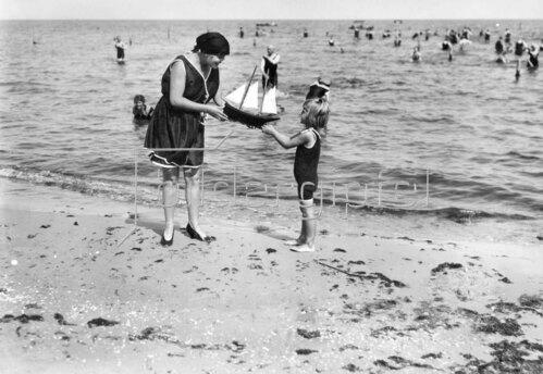 Insel Usedom, Heringsdorf: Frau überreicht kleinem Mädchen ein Modellsegelschiff am Strand 1919