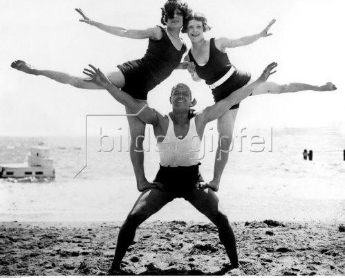 Mann und zwei junge Frauen bilden eine 'Pyramide' am Strand