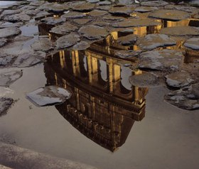 Colosseo reflected in puddle, after rain, roman street, Rom, Latium, Italien
