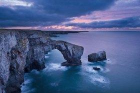 Sunrise over The Green Bridge of Wales, a natural rock arch on the coast, Pembrokeshire, Großbritannien, Pembrokeshire Coast National Park, Vereinigtes Königreich