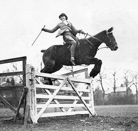Die passionierte junge Springreiterin Olive Ricks auf ihrem Pony-Pferd Peter Pan im Sprung in Addlestone, Surrey. Photographie