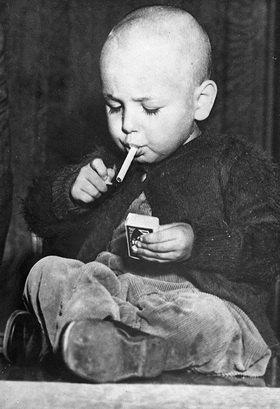 22 Monate alter Junge zündet sich eine Zigarette an. Los Angeles. Photographie