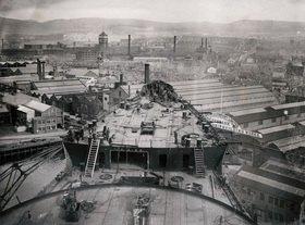 Bau des grö?ten und schnellsten Linienschiffs der Welt, des Schiffs 534 Britannia der Cunard Line: Schiffsbug vor den Schiffswerften und Arbeiterhäusern in Clyde Bank, Glasgow